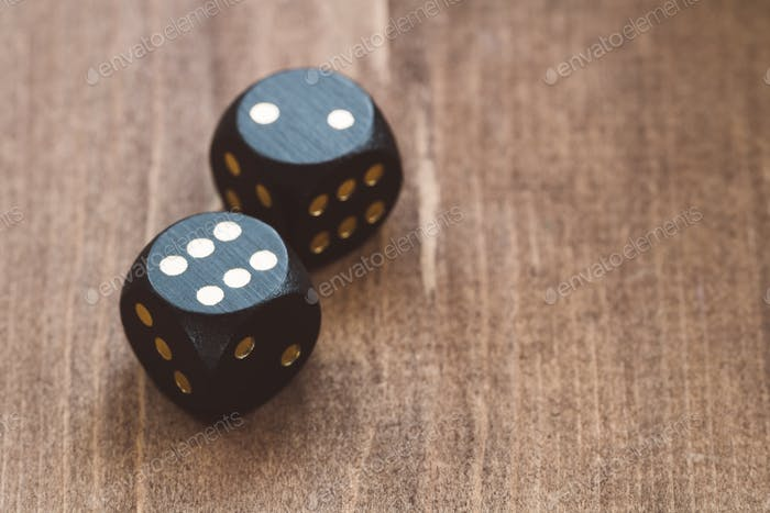 Close-up of black dice on a wooden table