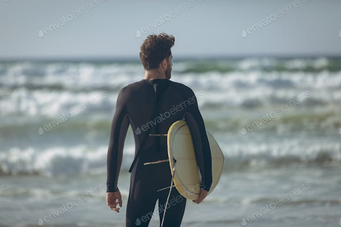 Young male surfer with a surfboard standing face to the ocean on a beach on sunny day