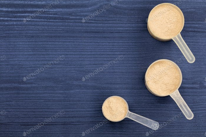 Scoops filled with protein powders on background blue wood