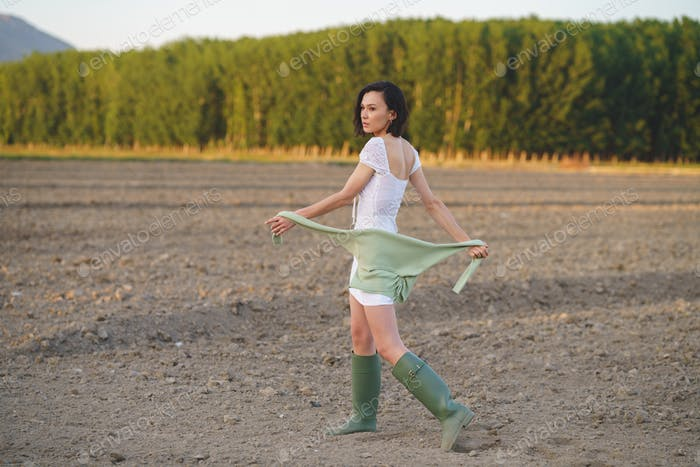 Asian woman, walking in the countryside, wearing a white dress and green wellies