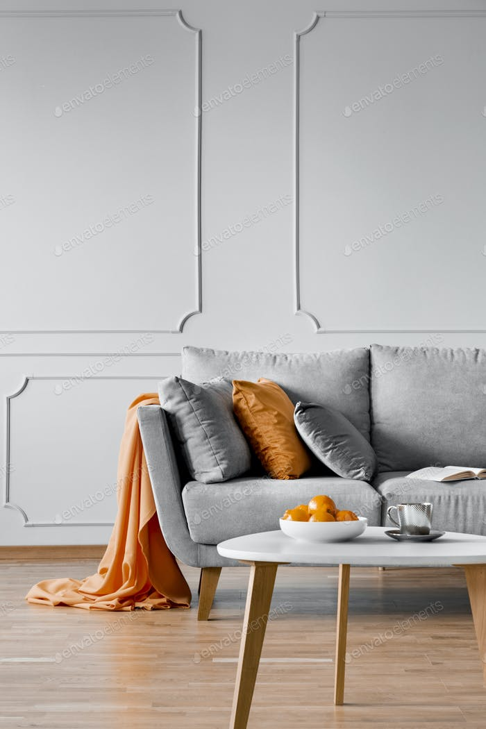 Silver, grey and orange pillows on scandinavian sofa, copy space on empty wall