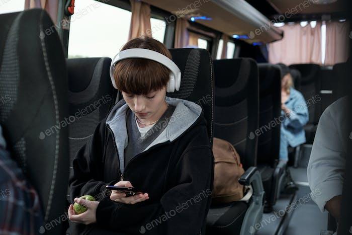 Cute teenage girl in headphones scrolling through playlist