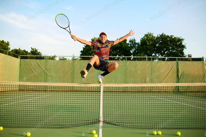 Happy male tennis player jumps with racket