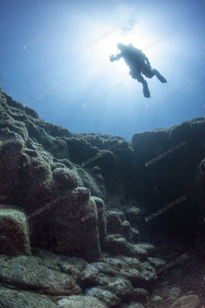 A Silhouetted Diver Floats Over Footsteps of the Giants Formation in Azores