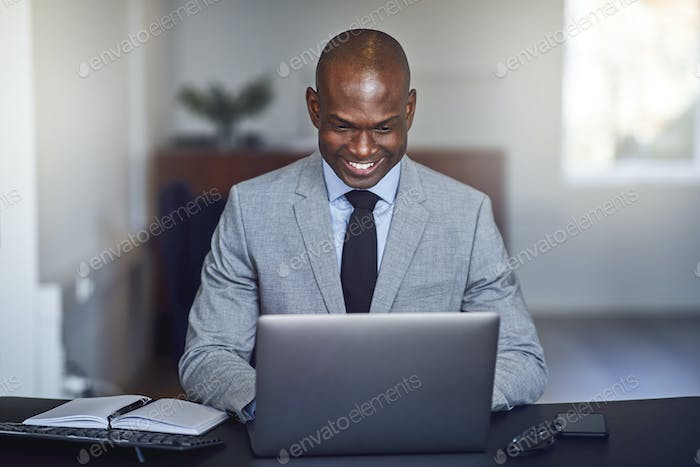 Smiling African American businessman using a laptop at work