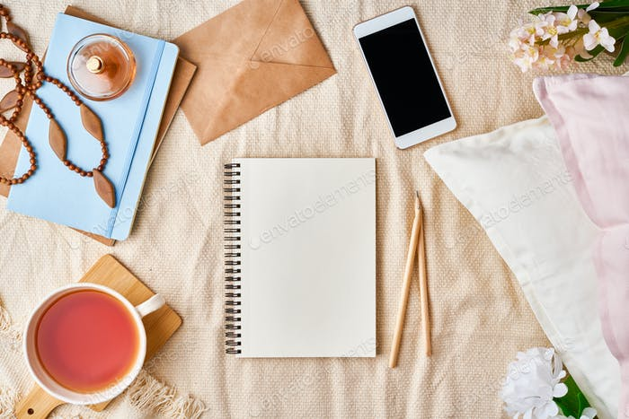 Mockup with notepad on bed and women's accessories, tea, cookies, pillows