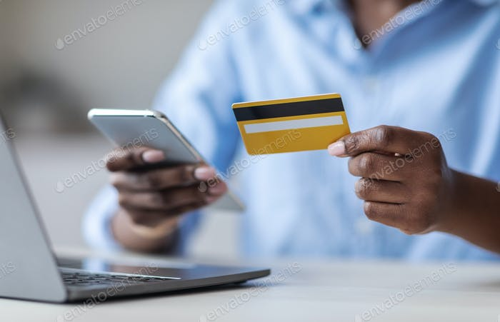Online Payment. Unrecognizable black female using smartphone and credit card in office