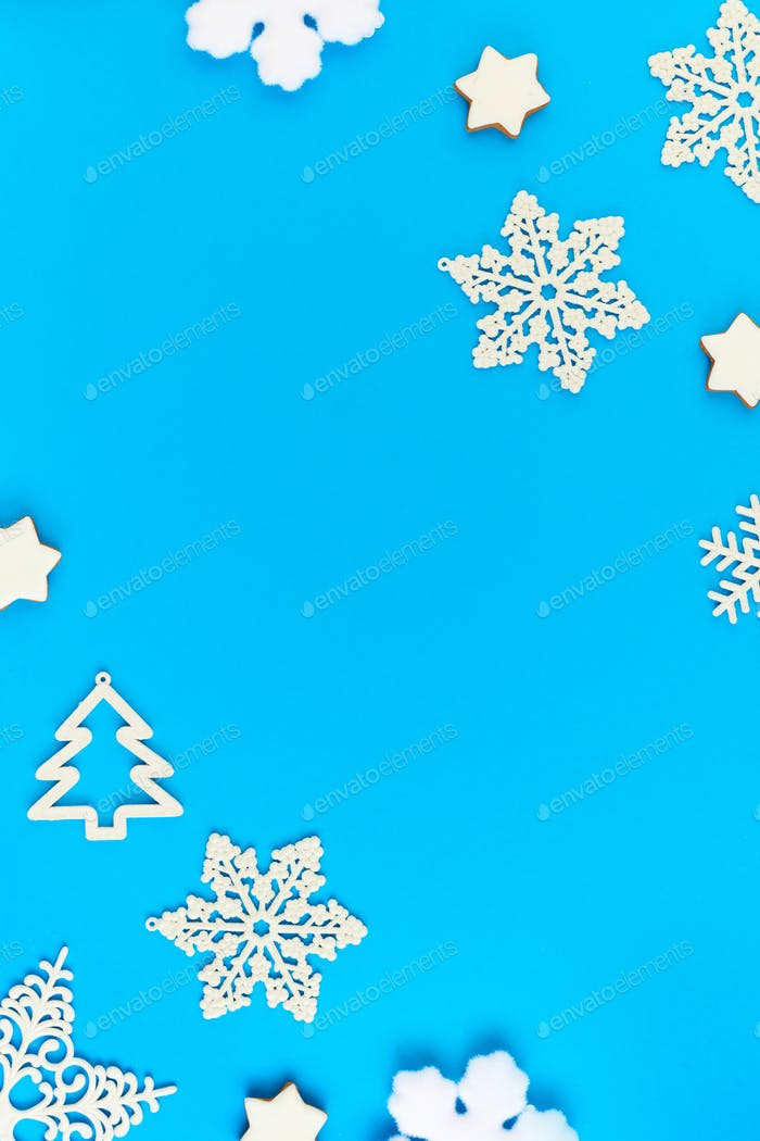 Flat layout of white snowflakes and firtrees surrounding copyspace for your text
