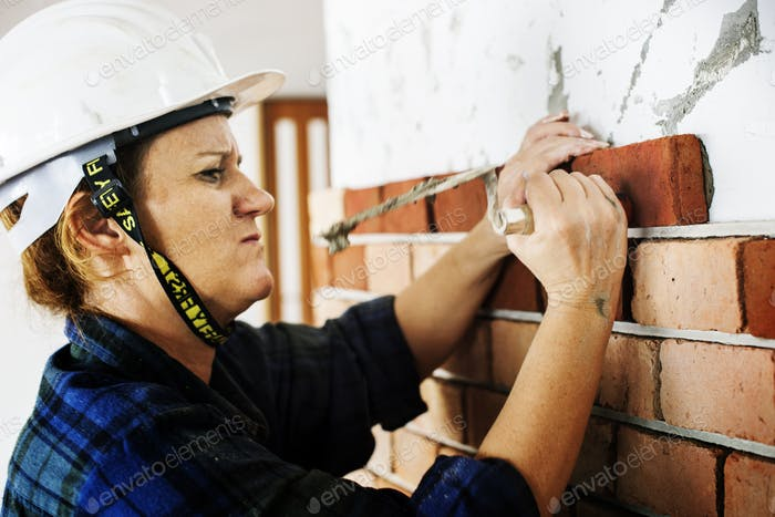 Woman construction repair plastering on the wall