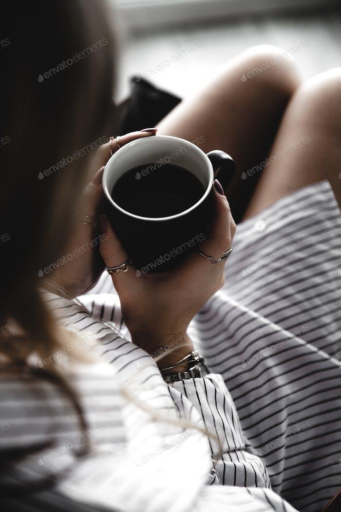 Taza de té y frío. Mujer acostada en el sofá, sosteniendo las piernas en la mesa de café, bebiendo café caliente