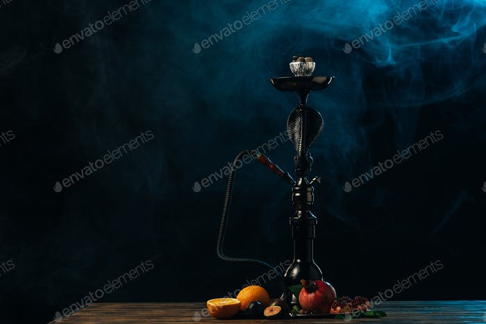 hookah with exotic fruits on wooden surface in blue smoke