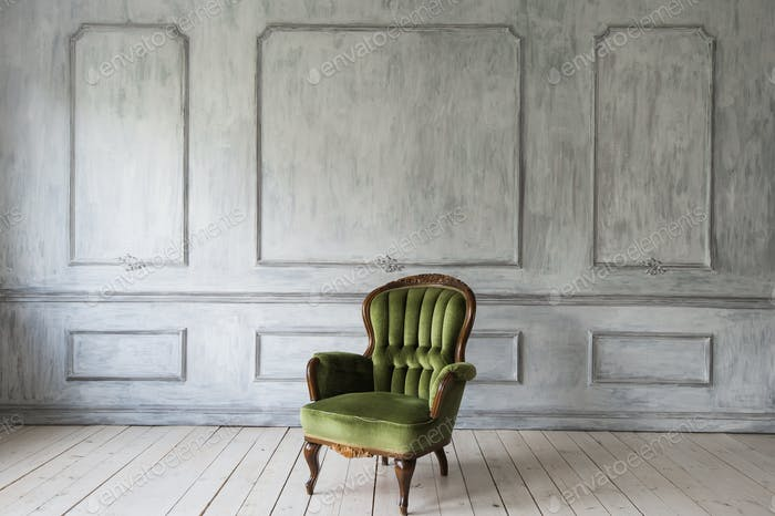 One classic armchair against a white wall and floor. Copy space