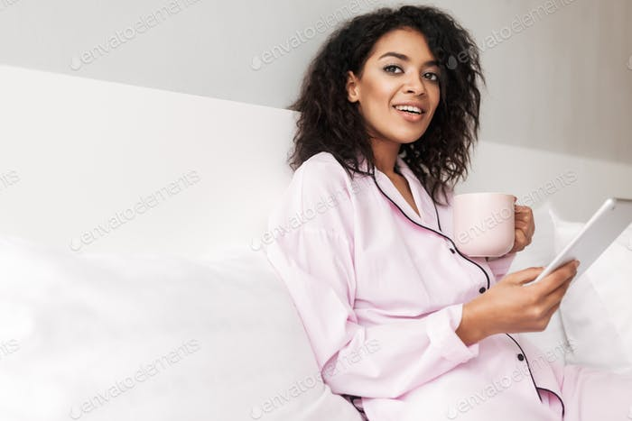 Lady with curly hair in sleepwear sitting in bed with cup and tablet in hands dreamily looking aside