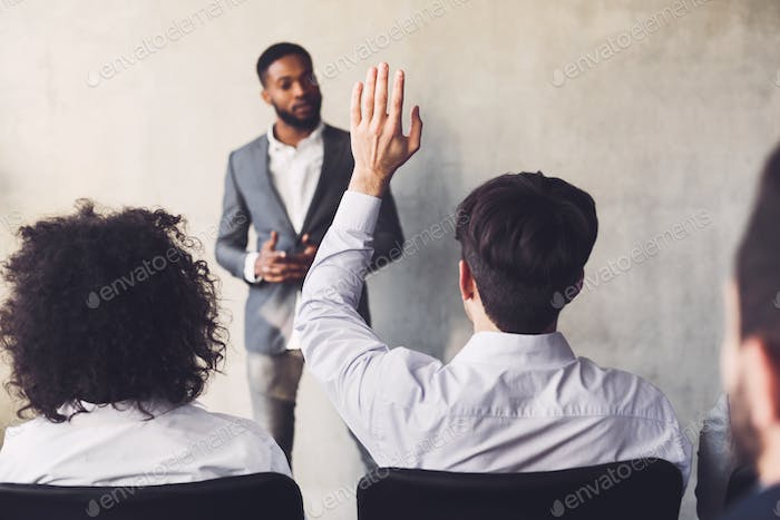 I have question. Businessman raising his hand