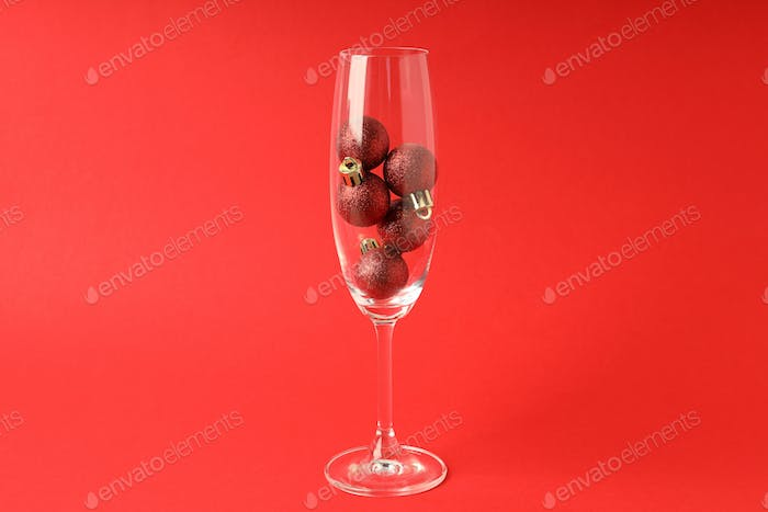 Champagne glass with baubles on red background