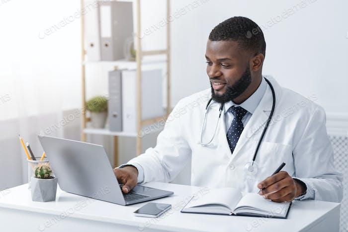 Freundliche schwarze Arzt machen Online-Check up, mit Laptop
