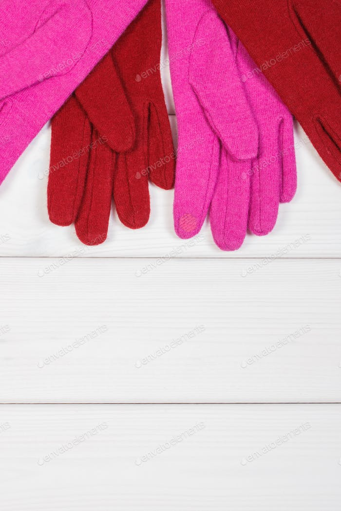 Colorful womanly gloves on boards, clothing for autumn or winter, copy space for text