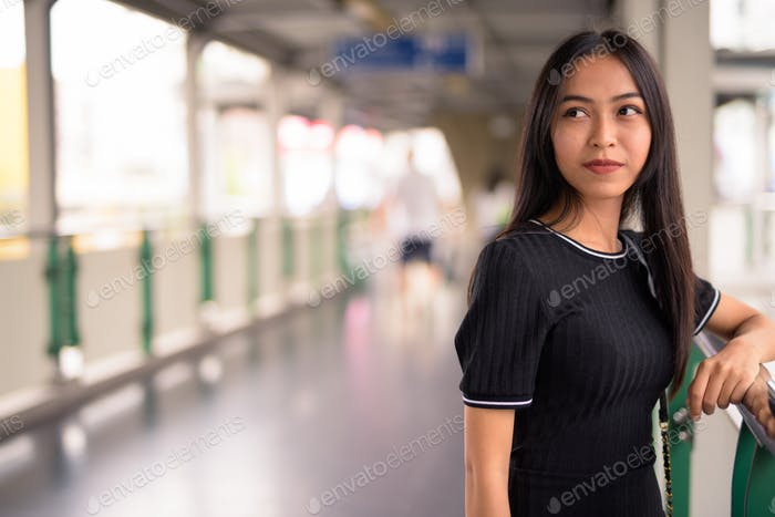 Young beautiful Asian tourist woman thinking on the footbridge