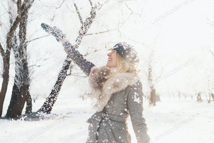 Eine lachende, glückliche Frau spielt mit Schneeflocken Ein Lachen, Hap