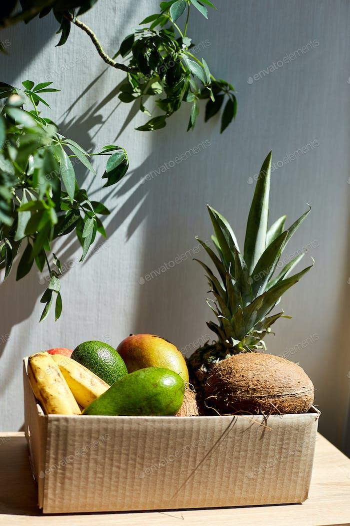Assortment of organic exotic fruits in box, sunlight.