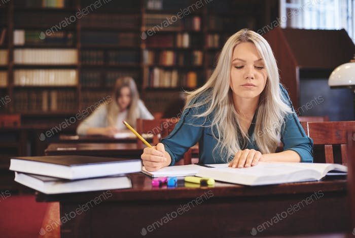 Woman working at desk taking notes