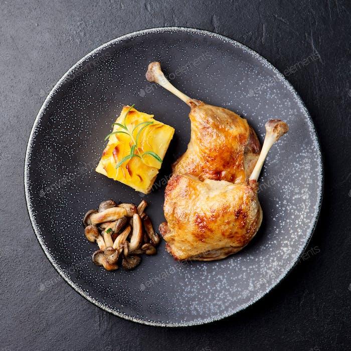 Entenschenkel Confit mit Kartoffelgratin und Pilzsauce. Restaurant serviert.