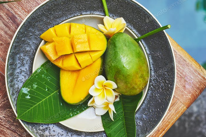Fresh mango on a wooden tabel with tropical background. Soft focus.