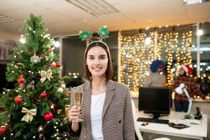 Pretty young office manager with flute of champagne cheering up with you