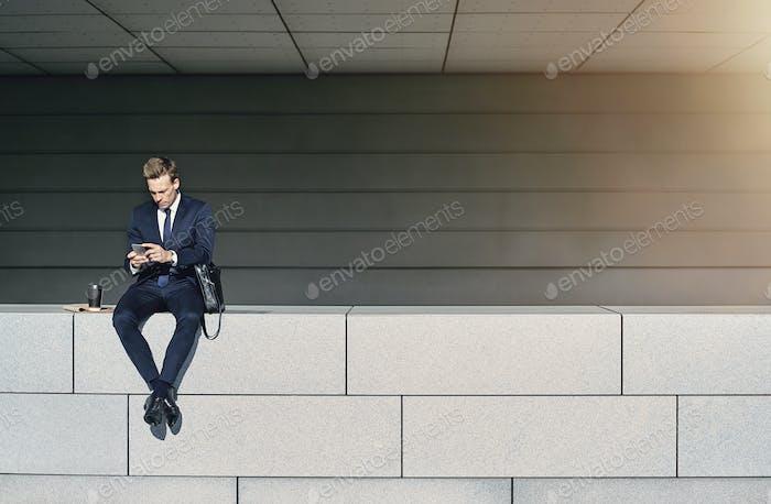 Männlich im Anzug sitzen und mit Telefon