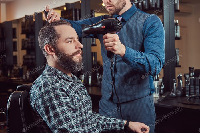 Professional barber working with a client in a hairdressing salon, uses a hair dryer.