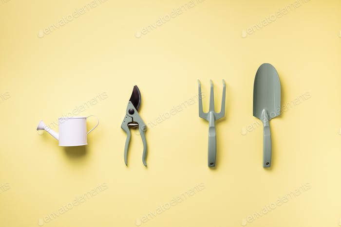 Gardening tools and utensils on yellow background. Top view with copy space. Pruner, rake, shovel