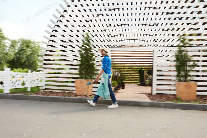 Gardener Walking Past Greenhouse