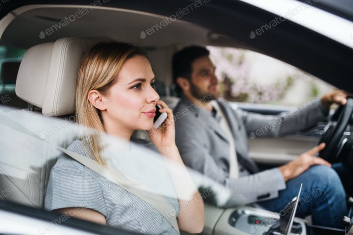 Happy young couple sitting in car, making phone call