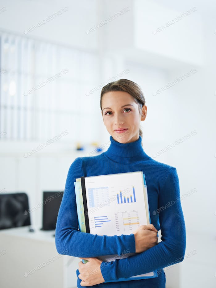 Young Female Secretary Looking At Camera Holding Folder