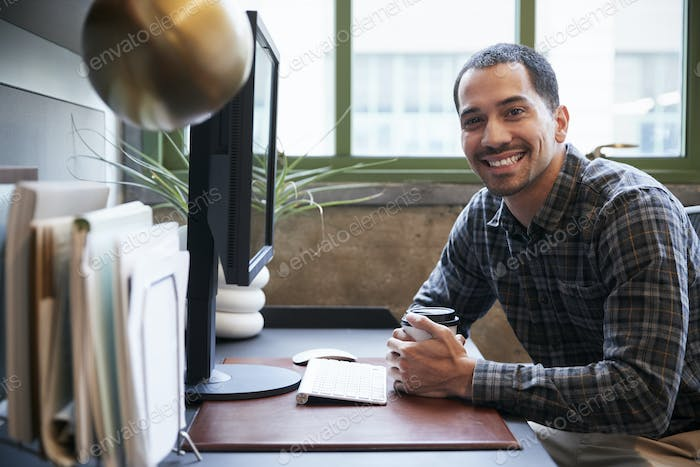 Hispanic man at a computer in an office smiling to camera