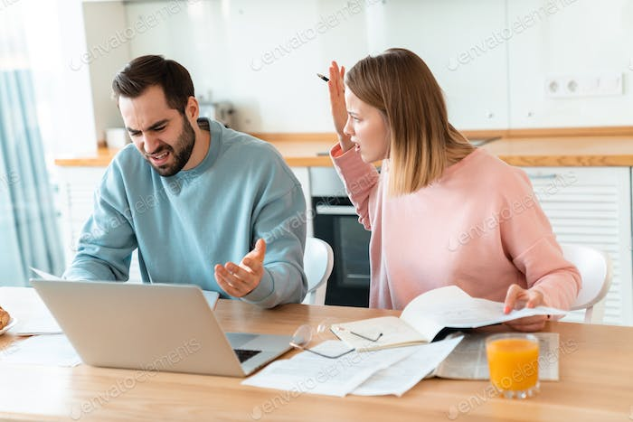 Portrait of young furious couple working with laptop and documents
