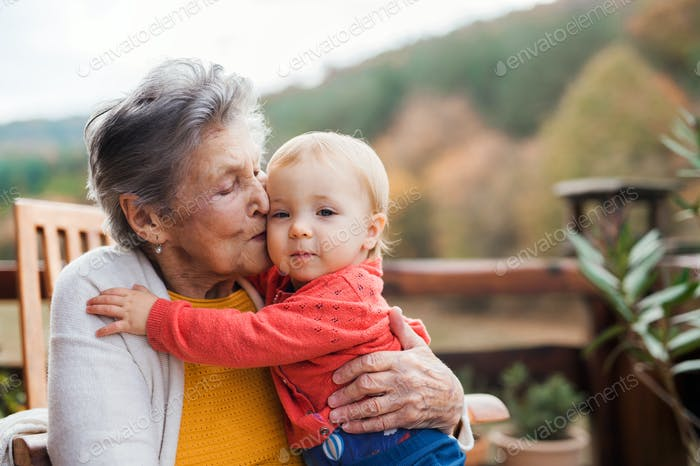 Elderly woman kissing a toddler great-grandchild on a terrace in autumn.