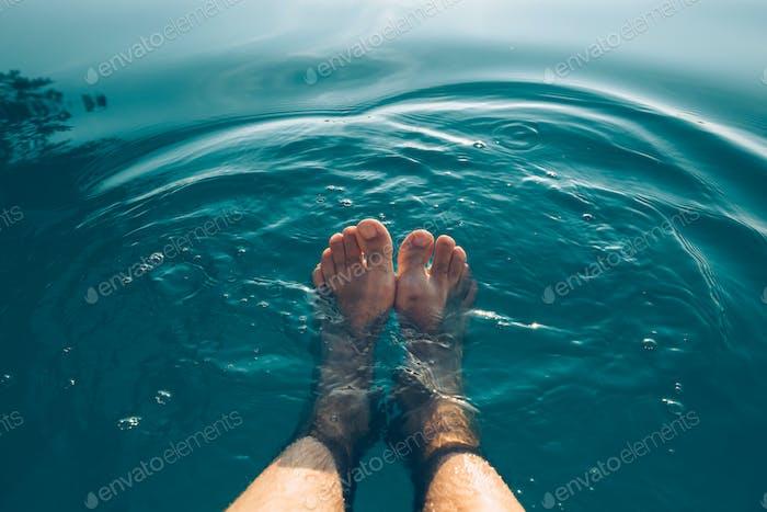 Männliche Füße im Außenpool