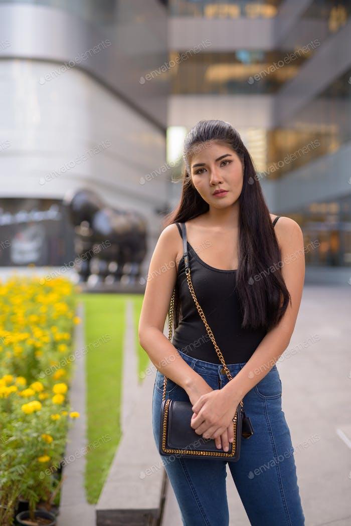 Young beautiful Asian woman exploring around the city