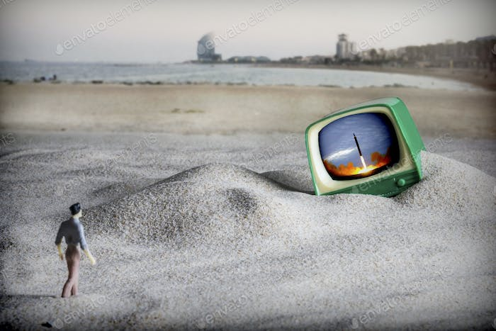 Dramatization of the end of the world, a man walks to an old television on the beach