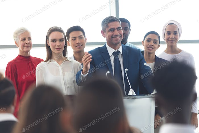 Businessman standing at podium with diverse colleagues and speaks at business seminar in office
