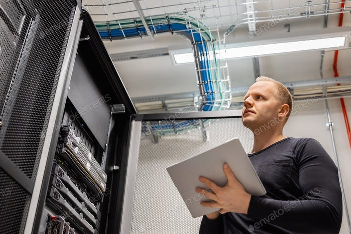 Adult Male Technician Holding Digital Tablet and Analysing Servers in Datacenter