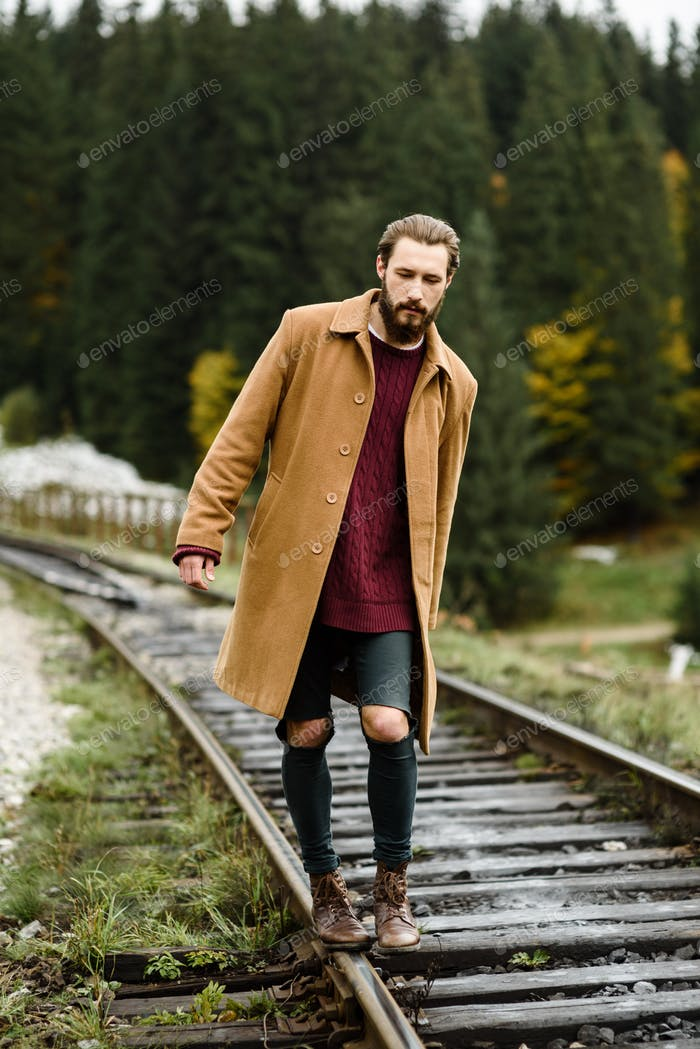 brutal bearded man walks on the tracks