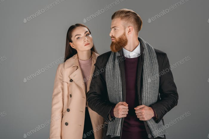 fashionable woman in autumn coat and man in jacket posing isolated on grey