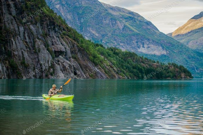 Hombres en Kayak en el Lago Glacial en Noruega