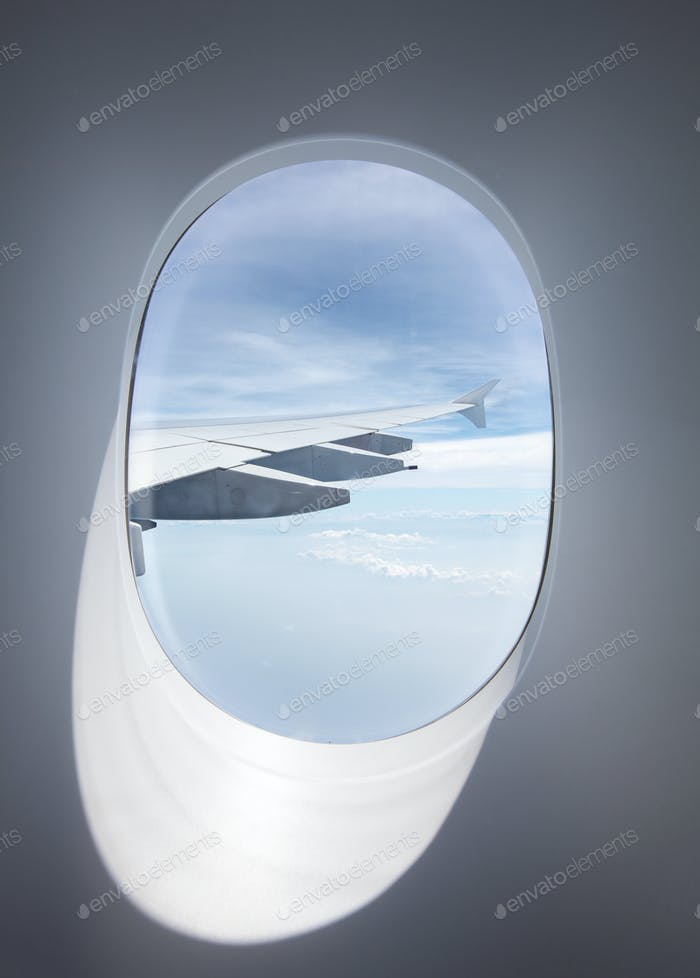 porthole of passenger plane with wing and clouds