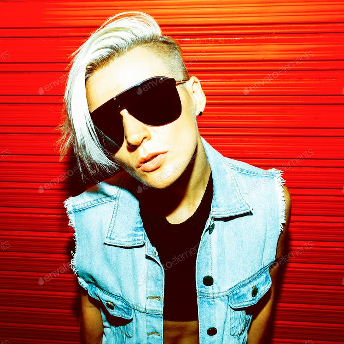 Blonde with short hair in stylish clothes and sunglasses on a re