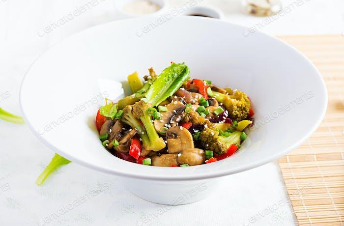 Braten Sie Gemüse mit Pilzen, Paprika, roten Zwiebeln und Brokkoli. Gesundes Essen. Asiatische Küche.