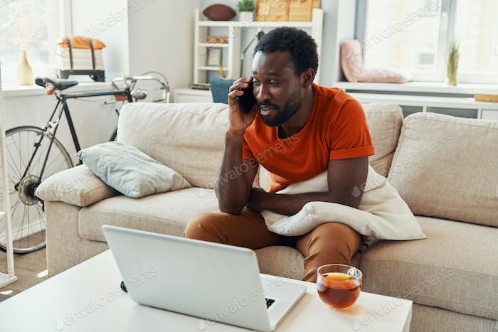 Handsome young African man talking on the phone and smiling while spending time at home