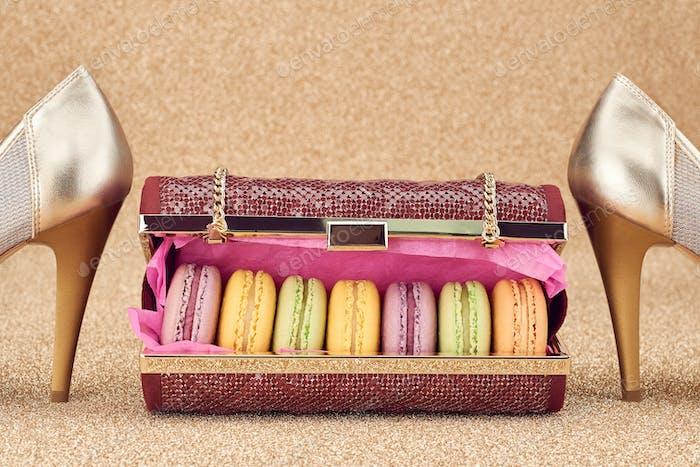 Macarons in fashion handbag, heels on gold.Vintage